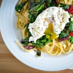 wilted greens and pasta with a poached egg in a browned lemon butter sauce